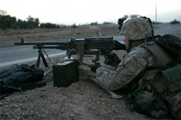 "A U.S. Marine from Weapons Platoon, Company E, 2nd Battalion, 1st Marine Regiment, 1st Marine Division, mans an M240G machine gun at the Highway 1 ""cloverleaf"" outside the city of Fallujah, Iraq, April 5, 2004. U.S. Marines islolated the city after t"