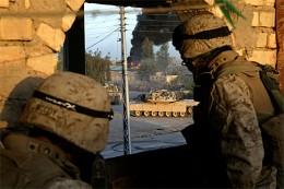 Marines of 1st Marine Regiment in Fallujah. Infantrymen from 1st Platoon, Company E, 2nd Battalion, 1st Marine Regiment, 1st Marine Division, look on from a rooftop as M-1A1 tanks from 1st Tank Battalion fire on buildings where enemy snipers took pos