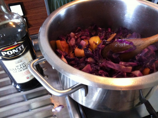 Cooking red cabbage and apple and onion in the pan with balsamic vinegar