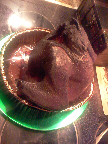 Completed beer can turkey is turned very dark by the hours of smoke permeating the skin and juicy meats of the bird.