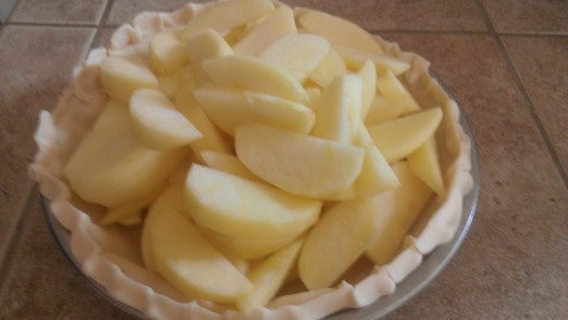 Sliced apples fill the prepared pie shell