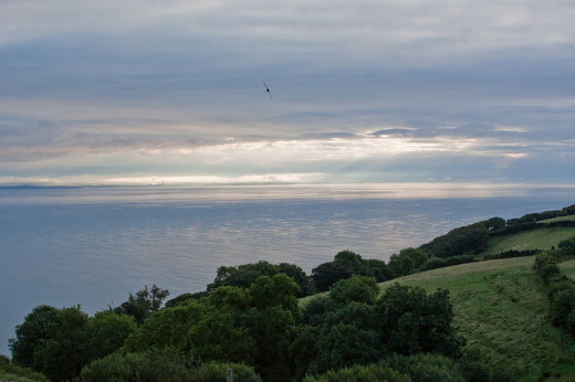 : A view towards the Bristol Channel from the first floor window of Silcombe Farmhouse, a B&B on the South West Coast Path, Somerset, England. Following heavy rain, early morning sunshine peeks through the clouds.