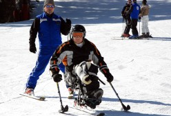 A war veteran learning to snow ski on a sit-ski, using two outriggers