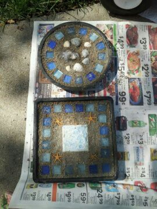 Mosaic cement stepping stones I make for my garden. Using tiles, seashells from beach visits and sea glass from craft stores. Lay the design on the ground or draw it out and then I push them into wet cement.