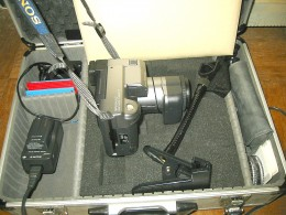 Sony Mavica-91 camera in its carrying case. To the right is a camera holder that can clamp onto a tabletop. To the left are batteries, battery charger, and a set of 3.5-inch floppy disks