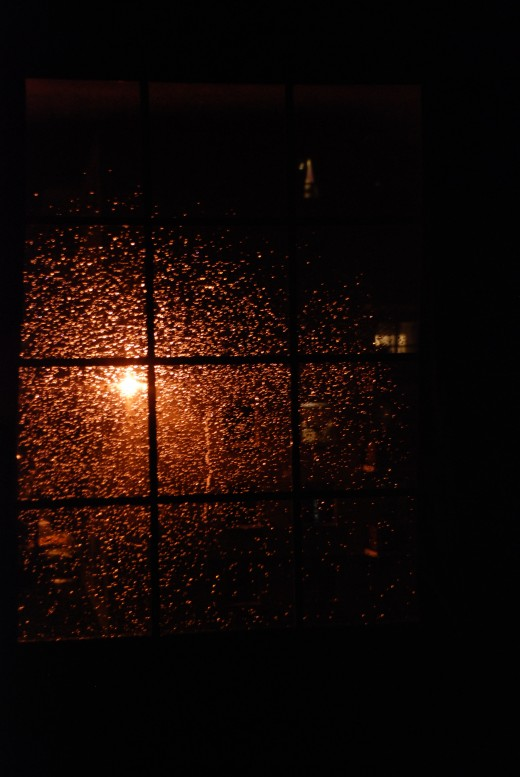 Night rain and raindrops reflecting orange colour amidst the dark room and an outdoor light source.