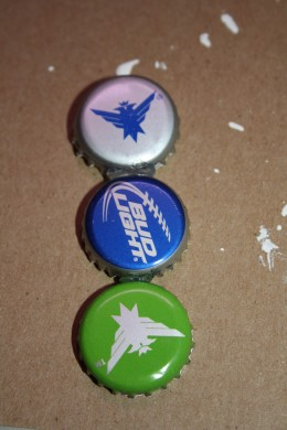 Use hot glue to glue three bottle caps together.