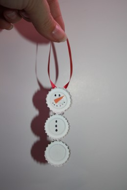 Draw on the eyes, mouth and butttons and hot glue a ribbon to the back of the snowmans head to hang him.