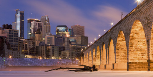 Minneapolis, viewed from the bank of the Mississippi, with the Stone Arch Bridge to the right.
