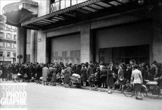 October - Line in front of the department store Le Bon Marche to exchange old rags for textile points redeemable for new clothing. Copyright LAPI/Roger-Viollet