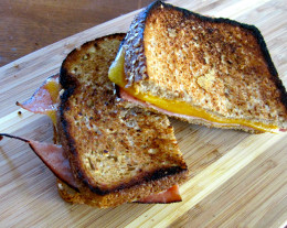 Grilled cheddar cheese with black forest ham and spicy hummus on whole grain bread.