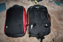 The back of the Osprey Porter packs.  The one on the left had the shoulder straps tucked in; the one on the right has the shoulder straps removed.  Having the ability to easily move between suitcase and backpack is extremely handy.