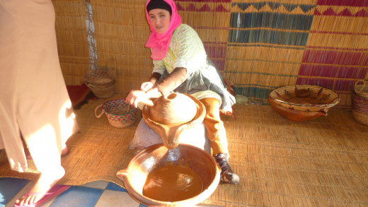 Moroccan woman grinding argan for oil.
