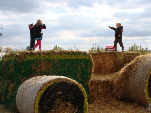 Climbing a John Deere tractor made from straw bales.