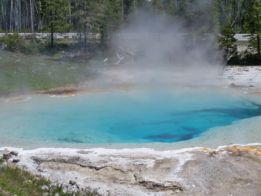Steam rises off of a hot spring - would not want to step anywhere near there.