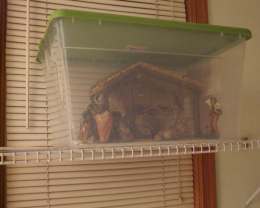A Christmas Nativity set up inside a plastic storage container on a high shelf to protect it from pet cats.