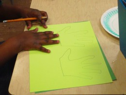 Carefully trace your hand on green construction paper.