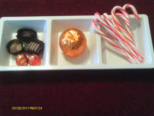 Holiday candy includes: chocolates, a chocolate orange, and candy canes.