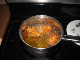 Frying fritters in pot of oil