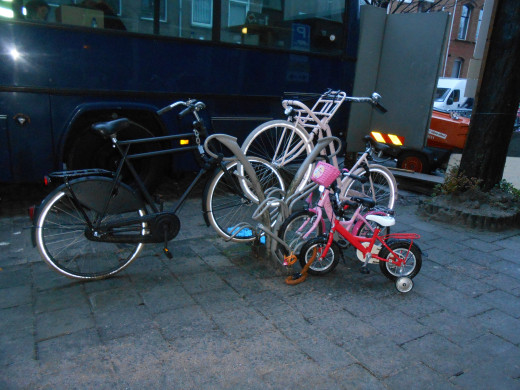 This looks like the family bike rack. There's a Dad's bike, a mom's bike and 2 kids bikes all on this one rack in a residential area.