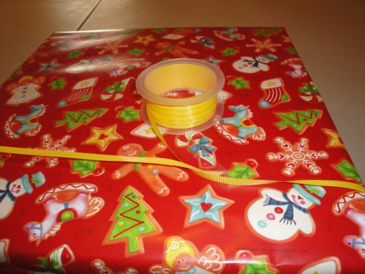 Step 3, optional; to add ribbon, tape front edge of ribbon to back of package, wrap around and bring the rest of the ribbon through behind the tape.  Wrap the other direction, tape end of ribbon, cut your ribbon after you tape it!