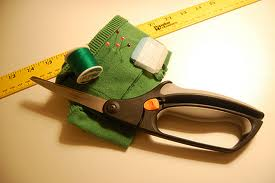 Supplies needed to change a pullover to a full zipper closure. A yard stick, pins, thread, scissors, chalk and an iron.