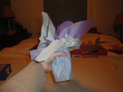 Using your hands, carefully pull the tissue paper up on each side of gift.