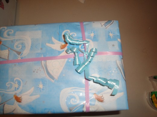 Wrap your ribbons around your package, then tie some pieces of curling ribbon to where the ribbons cross!