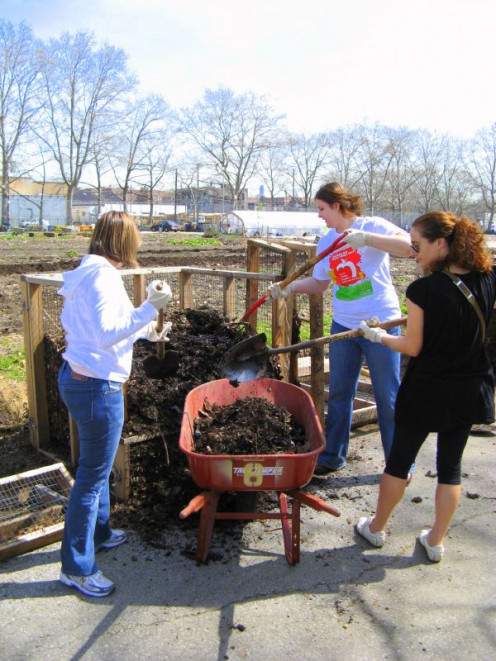 Women loading compost into a wheelbarrow and making a difference to save the environment.