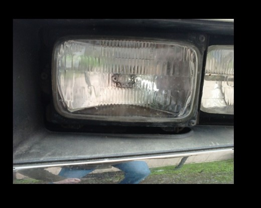 Headlamp on 1989 Chevy. Notice the screws holding the bezel on and the adjusting screw at the far left.