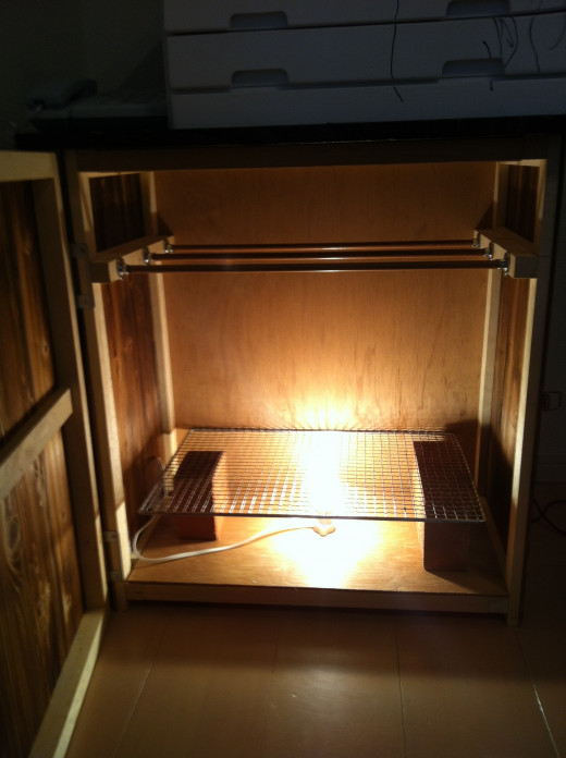 It has a 60 watt light bulb inside to provide the dry air that is needed for drying the strips of beef.