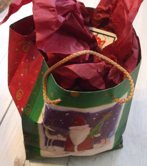 Brightly colored Christmas gift in gift bag with tissue paper.