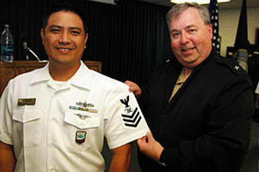 Rear Admiral Terry McCreary presenting a rating insignia of Mass Communications Specialist First Class (MC1)