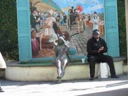 One of the statues of a lady sitting beside a real man near the waterfront in New Orleans.