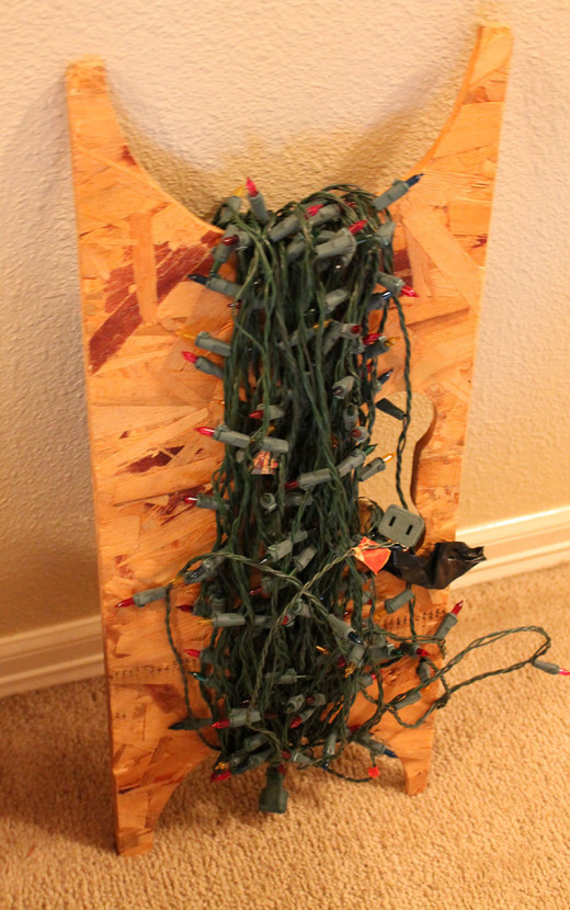 Scrap plywood make grate tangle free storage for Christmas lights.