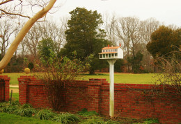 A manor-shaped birdhouse fronts the low brick wall that separates Sotterly Garden from one of the lanes on the property.