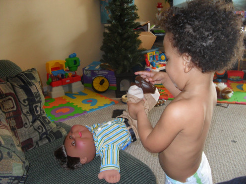 My son dressing his baby doll