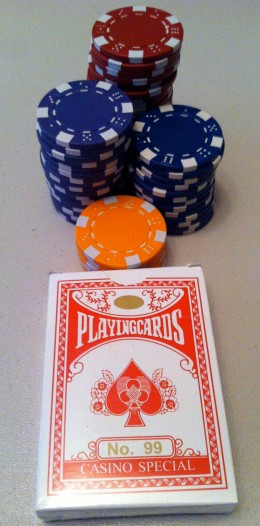 A set of composite poker chips with a deck of playing cards.