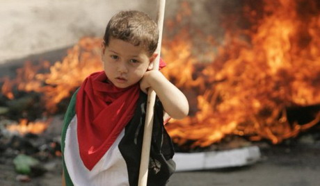 """A Palestinian child stands next burning tires at the Palestinian refugees camp on June 6, 2011 during a """"Day Of Rage"""""""