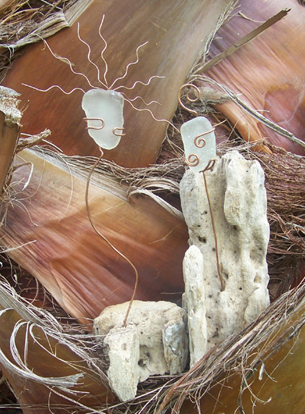 Two driftwood friends with wire and sea glass heads chat about the fairies they're seeing in the garden.