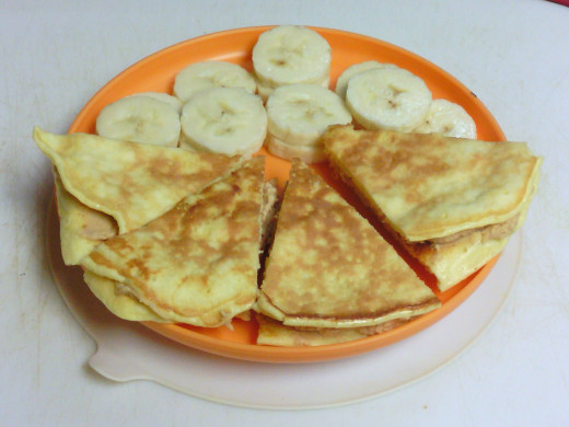 Protein pancake sandwich (filled with banana and peanut butter Greek yogurt) and sliced bananas.