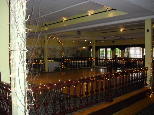Wedding and reception venue with the dance floor to the left and tables surrounding it.