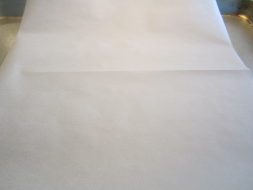 Fold the parchment paper in half to create a crease for easy handling.