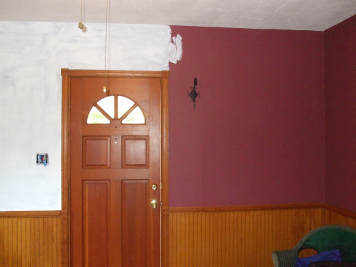 Applying primer over deep burgundy walls in a living room.
