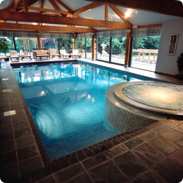 Modern Indoor Swimming Pool with Round Hot Tub with natural wood beams, stone floor and sliding doors