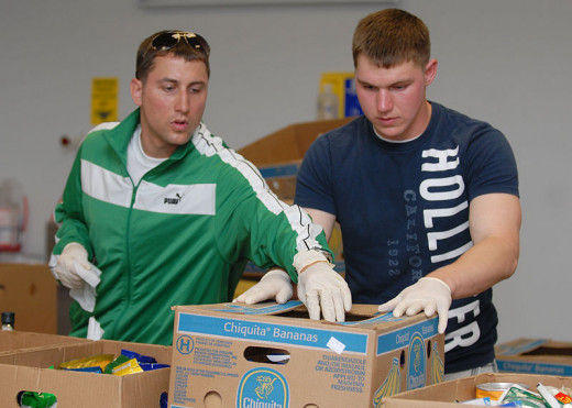 Cryptologic Technician (Repairman) 2nd Class Richard Swank and Information Systems Technician Seaman Michael Cunningham volunteering on April 20, 2009 at a food bank in Charleston, South Carolina