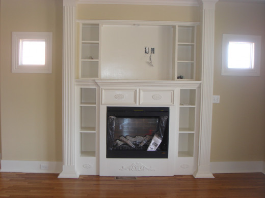 When this all electric house was renovated, a fireplace with shelving and detailed woodwork was added.
