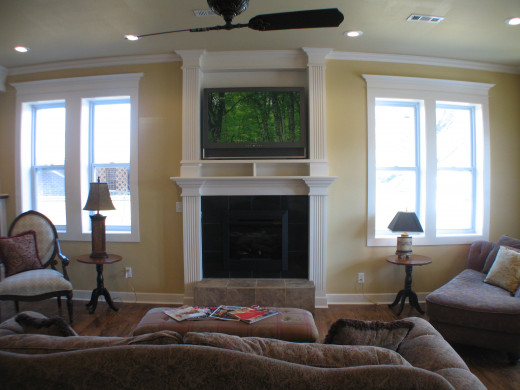 This fireplace was added specifically to house a TV and its components.  The woodwork ties into the window surrounds.