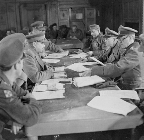 Lieutenant-General Charles Foulkes (left centre), GOC 1st Canadian Corps, accepts the surrender of German forces in The Netherlands from General Johannes Blaskowitz, Wageningen, The Netherlands, May 5, 1945 Credit: Alexander M. Stirton/Canada. Dept.