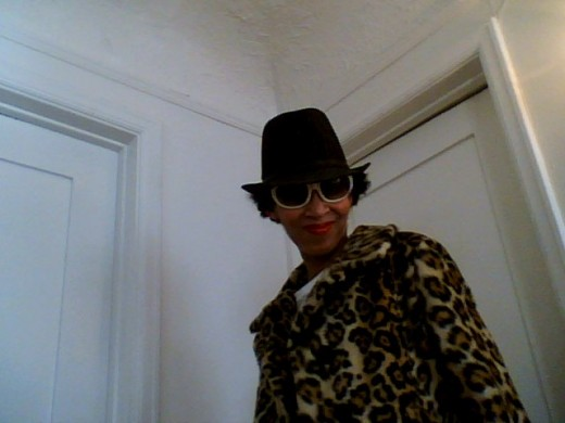 Victoria Moore in a vintage leopard coat, pinstriped fedora, vintage shades and peach 1970s style roller skating tee.
